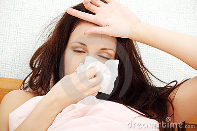 Beautiful woman seezing in a tissue.