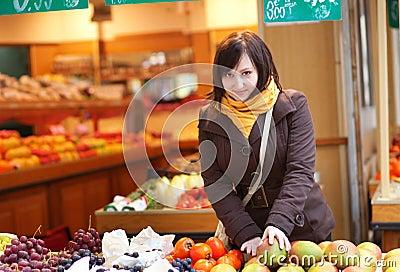 Beautiful woman selecting fresh mangoes