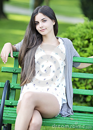 Beautiful woman sitting on bench - Outdoor