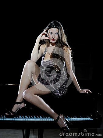 Beautiful woman sitting on a black studio piano