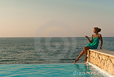Beautiful woman sitting near infinity pool