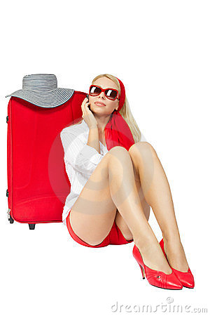 Beautiful woman sitting next to red suitcase