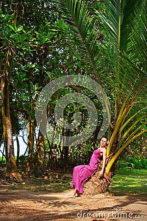 Beautiful woman sitting on the palm