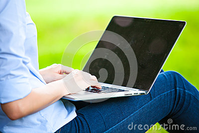 Beautiful woman sitting in park with laptop