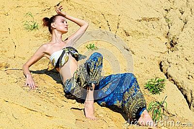 Beautiful woman sitting on the sand
