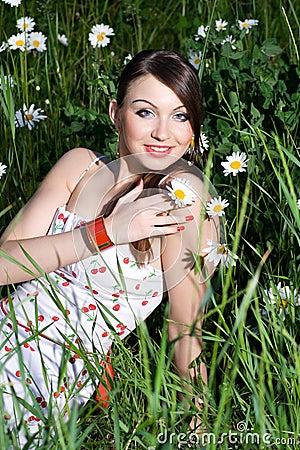 Beautiful Woman Sitting in tall grass & daisies