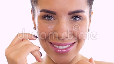 Beautiful woman rubs cream in face at white background. Beautiful woman smears her face with cream. Pretty brunette smiles to camera and gently touches her stock footage