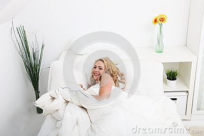 Beautiful woman snuggling down in bed