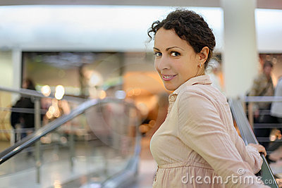 Beautiful woman standing on escalator
