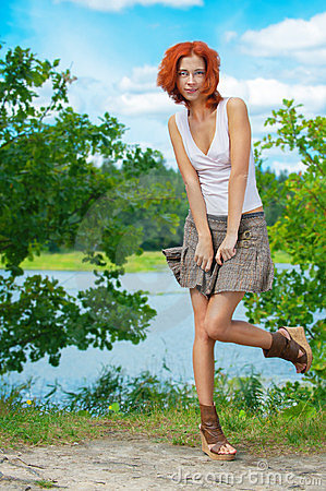 Beautiful woman standing near lake