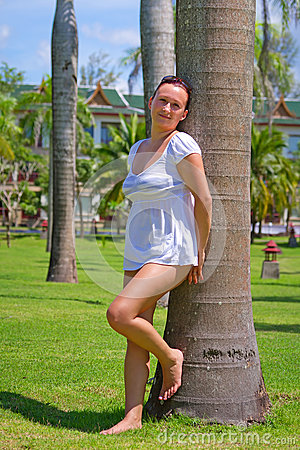 Beautiful woman standing under palm tree