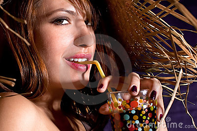 Beautiful woman with straw hat drinking  juice