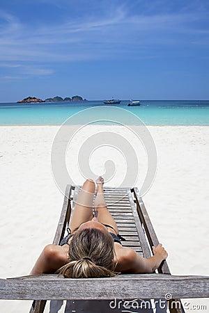 Beautiful woman sunbathing in paradise.