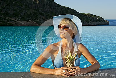 Beautiful woman in the swimming pool near coast