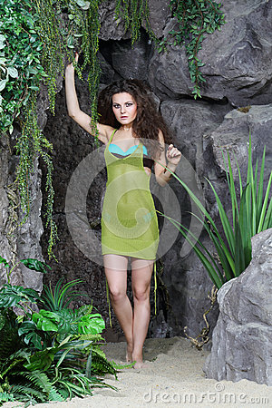 Beautiful woman in swimsuit and jersey stands next to  rocks