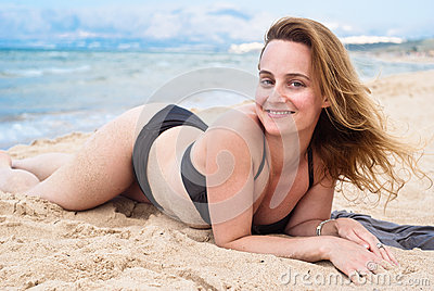 Beautiful woman in swimsuit relaxing on a beach