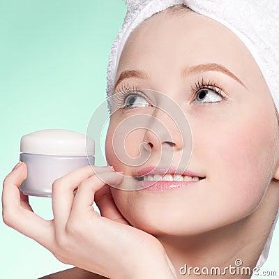 Beautiful woman tender jar of moisturizer cream