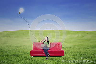 Beautiful woman thinking on red sofa under lamp outdoor