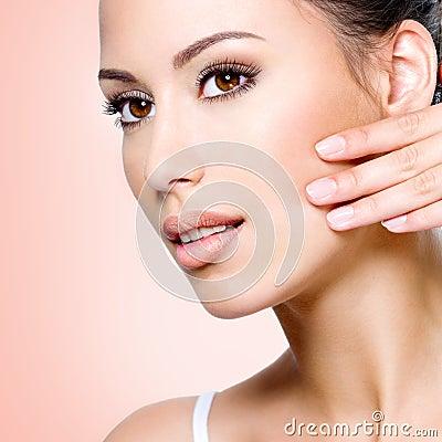 Beautiful woman touching skin of  face