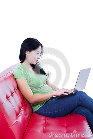 Beautiful woman typing on red sofa - isolated