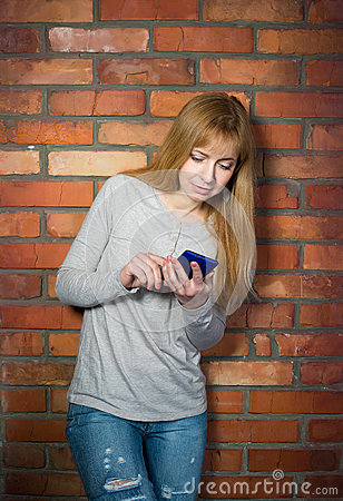 Beautiful woman using high tech smartphone against brick wall.