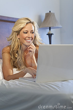 Beautiful Woman Using Laptop Computer In Bed