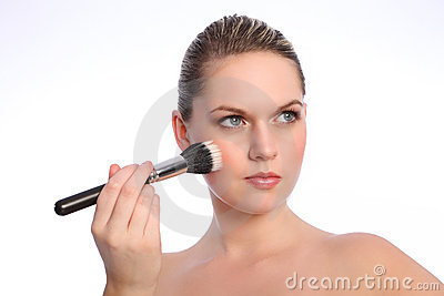 Beautiful woman using stippling make up brush