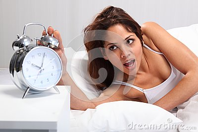Beautiful woman waking up reaching for alarm clock