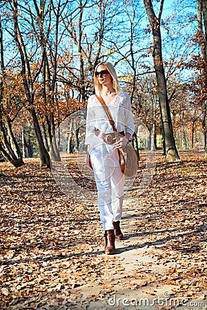 Beautiful  woman walking in the autumn  park
