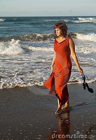 Beautiful woman walking with dress by the seaside