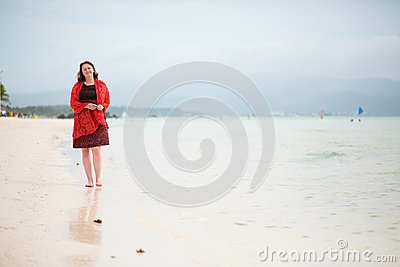 Beautiful woman walking by perfect white sand beach