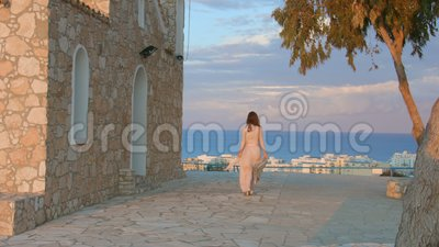 Beautiful woman walks on sidewalk, stops to enjoy amazing sea view. Resort town. Stock footage stock video