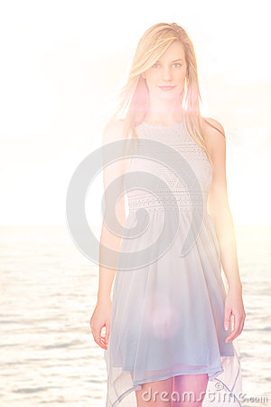 Beautiful Woman Wearing Casual Dress Standing Against Sea In Bac