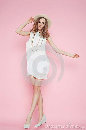 Beautiful woman in white dress posing on pink background in hat