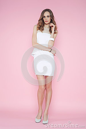 Beautiful woman in white dress posing on pink background