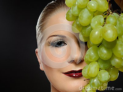 Beautiful woman with white grapes