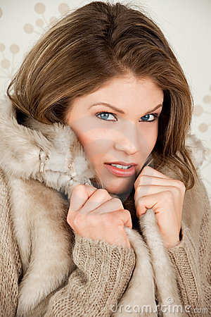 Beautiful woman in winter coat feels cold