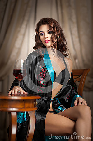 Free Beautiful Woman With Glass Of Wine Sitting On Chair. Portrait Of A Woman With Long Curly Hair Posing Challenging Stock Photo - 37873370