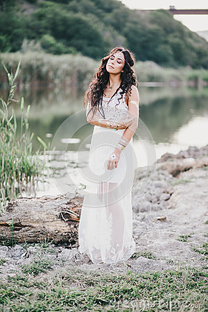 Free Beautiful Woman With Long Curly Hair Dressed In Boho Style Dress Posing Near Lake Stock Photos - 58695933