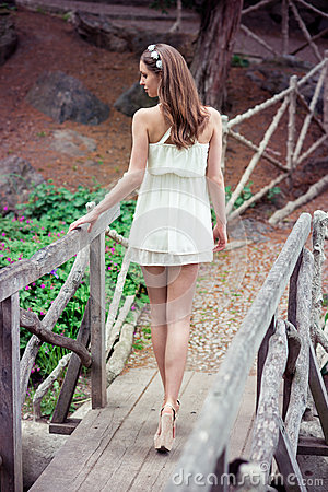 Free Beautiful Woman With Long Legs Wearing White Dress Walking At The Bridge In The Forest Stock Images - 54373734