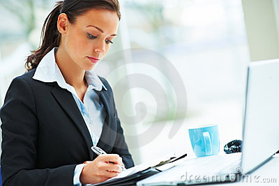 Beautiful Woman Writing And A Laptop In Front Royalty Free Stock Image - Image: 8327966