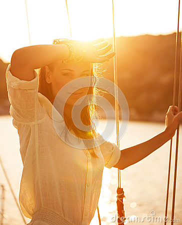 Beautiful woman on yacht on sunset