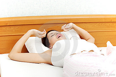 Beautiful woman yawning and stretching in bed.