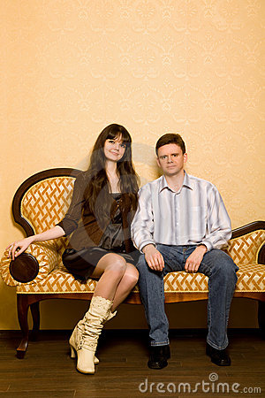 Beautiful woman and young man sitting on sofa