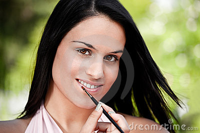 Beautiful women applying lipstick
