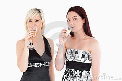 Beautiful women in dresses drinking champaign