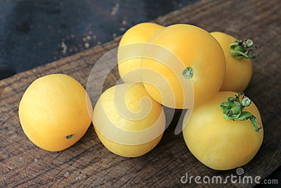 Beautiful yellow tomatoes on a wooden background
