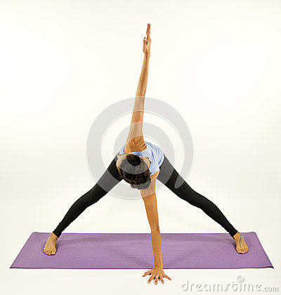 Young woman practices yoga moves and positions in a studio setting