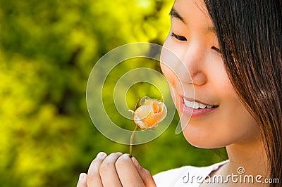 Beautiful Young Asian Woman Looking at Rose Bud