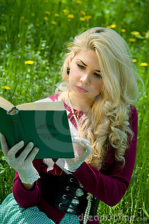 Beautiful young blond with book in summer park